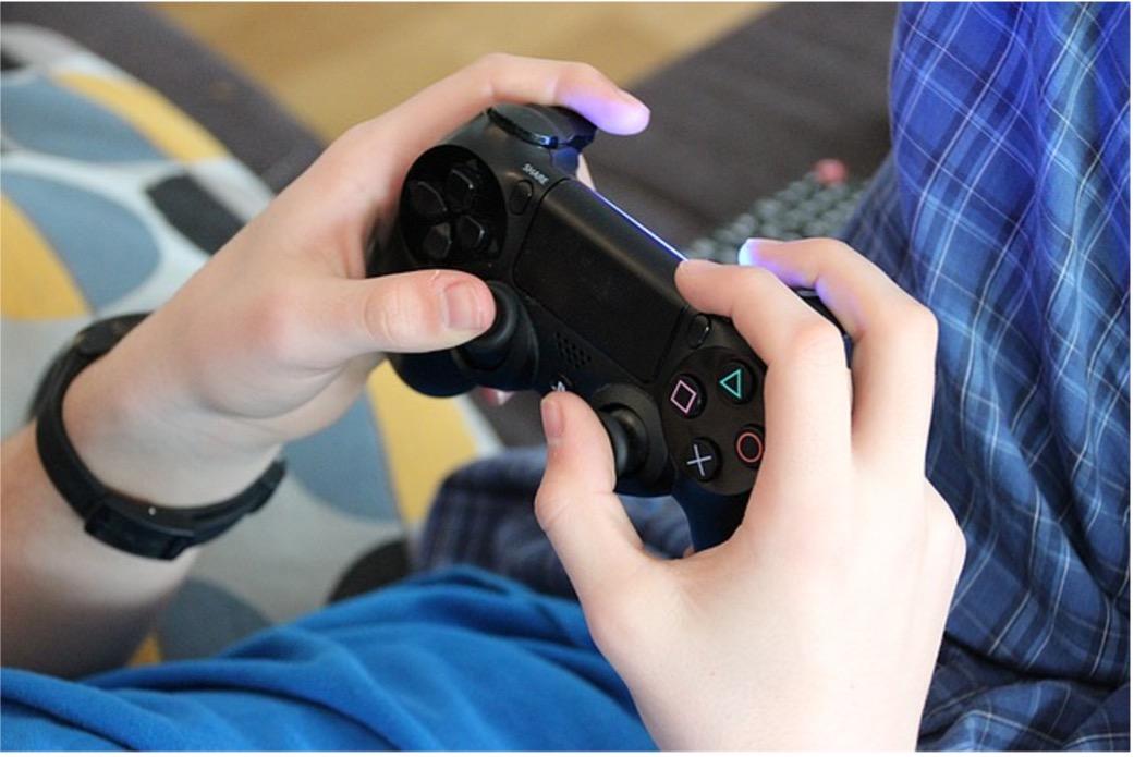 Joven jugando videojuegos con control de PS