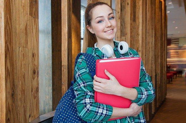 Estudiante con audífonos sosteniendo libro.