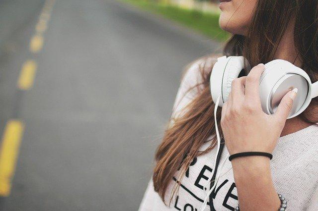 Mujer escuchando música mientras camina por la carretera.