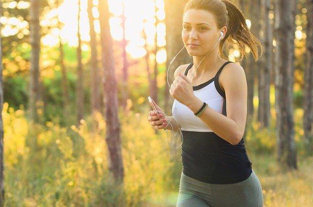 Mujer corriendo en parque mientras escucha música.