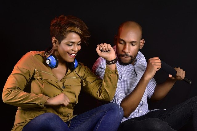 Pareja bailando mientras escuchan música juntos.
